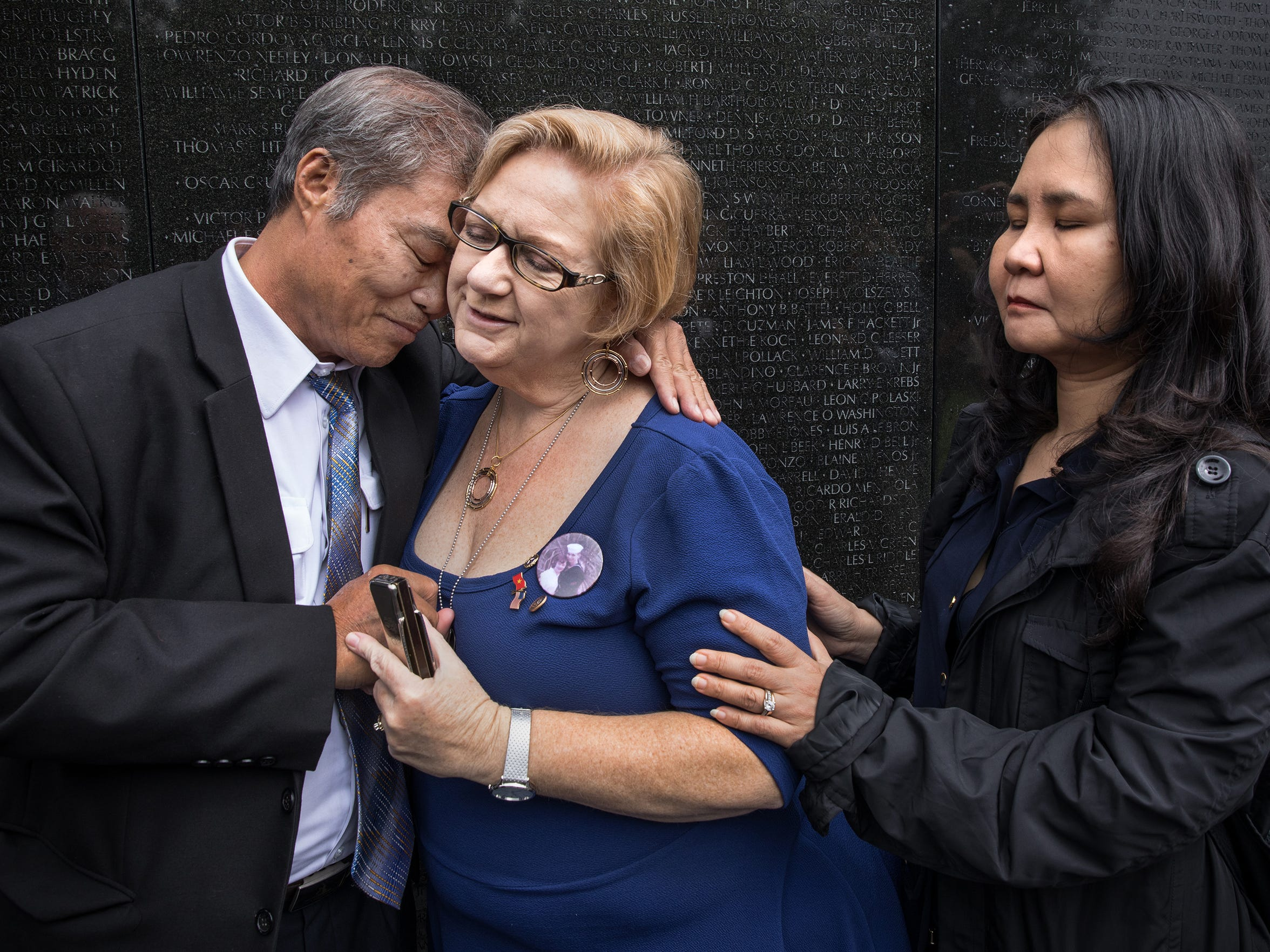 People whose parents died fighting on opposing sides in the Vietnam War held a ceremony Thursday at the Vietnam Veterans Memorial. Vu Ngoc Xiem, left, whose father was killed in an air raid, hugged Susan Mitchell-Mattera, whose father died in a helicopter shoot-down. Nguyen Thi Hong Diem, at right, lost both parents, who were members of the Viet Cong.