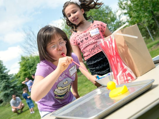 Jessica Schaller, 12, plays a duck-racing game while cheered on by sister Morgan, 9, during the David's Refuge picnic Saturday at the Pieters Family Life Center in Henrietta. Twelve-year-old Jessica Schaller, left, plays a duck racing game, cheered on by her sister Morgan Schaller, 9, right, during the Pieters Family Life Center picnic, June 10.