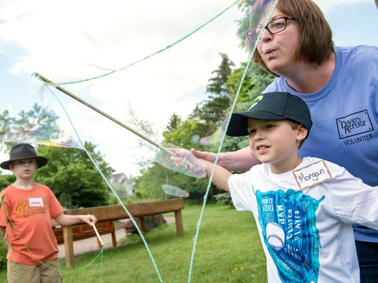 Morgan Greenlaw, 5, creates a big bubble, aided by volunteer Donna Miller, while Reese Greenlaw, 9, looks on at the David's Refuge picnic Saturday, June 10, at the Pieters Family Life Center.