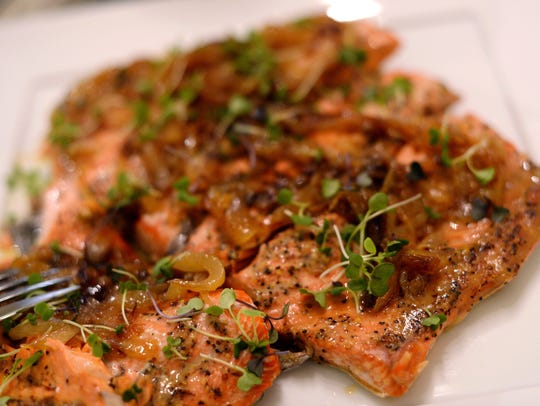 Homemade salmon with caramelized onions and micro greens