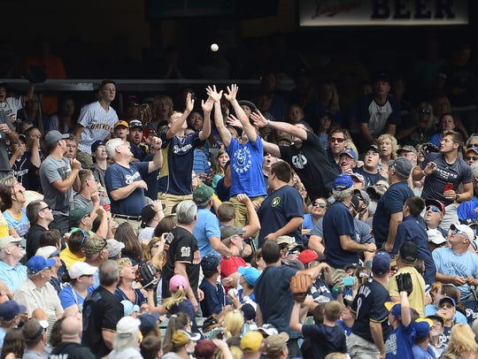 Fans reach for a foul ball during the first inning