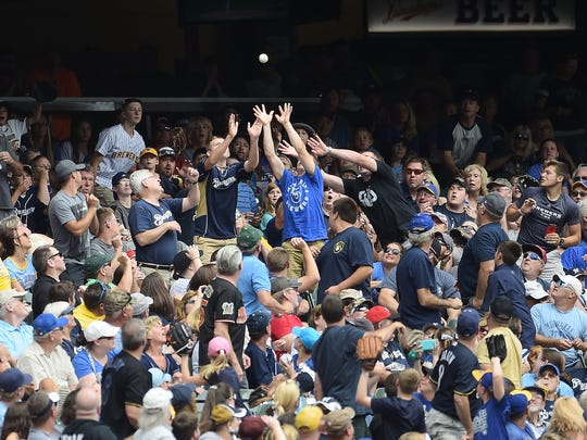 Fans reach for a foul ball during the first inning of a game between the Milwaukee Brewers and the Cincinnati Reds at Miller Park on Aug. 13, 2017.
