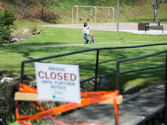 Kelly Rugiero of Greenville walks with her son, David, 1, by a bridge that is closed for renovations in McPherson Park on Friday, April 7, 2017.