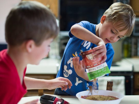 From left, Michael Tidrow, 8, watches as his brother