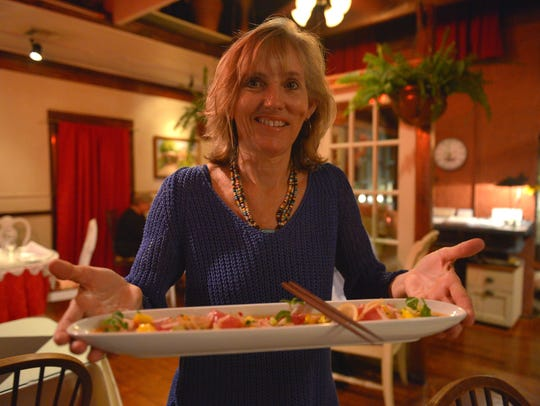 Margie Perrin shows off a dish made by her husband,