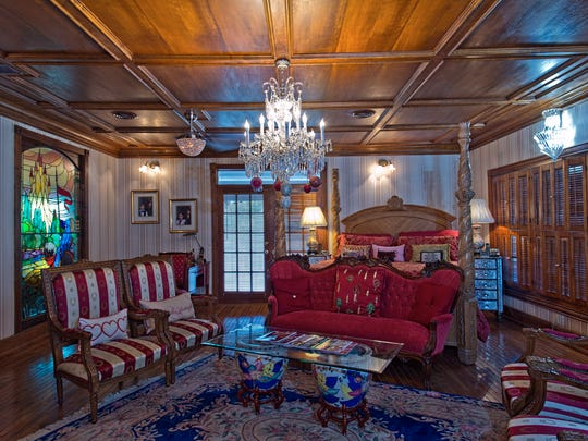 The master suite is lit by a large crystal chandelier on a wood paneled coffered ceiling and features a large stained glass window from the study area in the the room which has plenty of space for a great sitting area