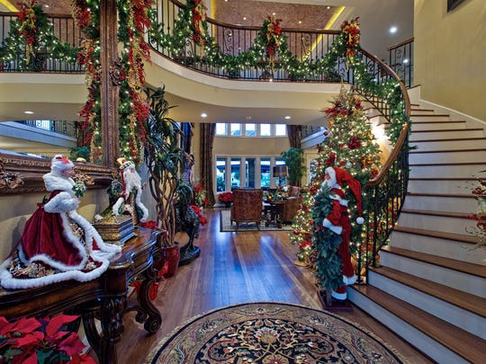 The garland lined winding staircase rises above the wood floored entry foyer greeting visitors with holiday cheer.