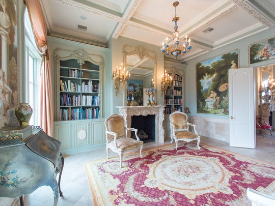 The formal library features gold leaf accents on doors,