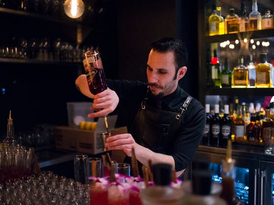 Mixologist Yani Frye pours drinks before dinner on