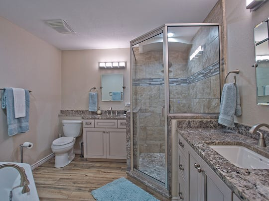 The master bath has a glass enclosed shower, a soaking tub and gorgeous granite counters