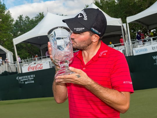 Julian Etulain kisses his trophy after winning the 2018 Chitimacha Louisiana Open at Le Triomphe Golf and Country Club.