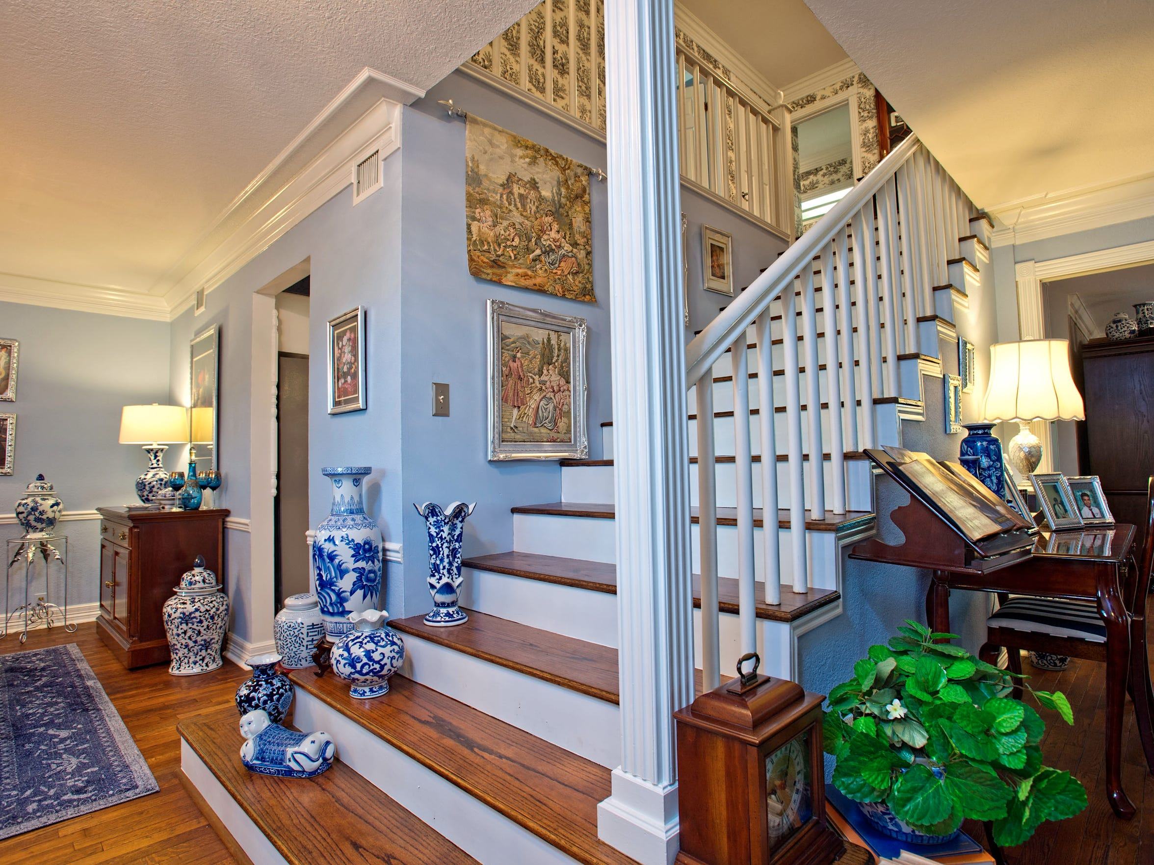 A wide hardwood open staircase is perfectly situated in the living space and is a great spot to display art
