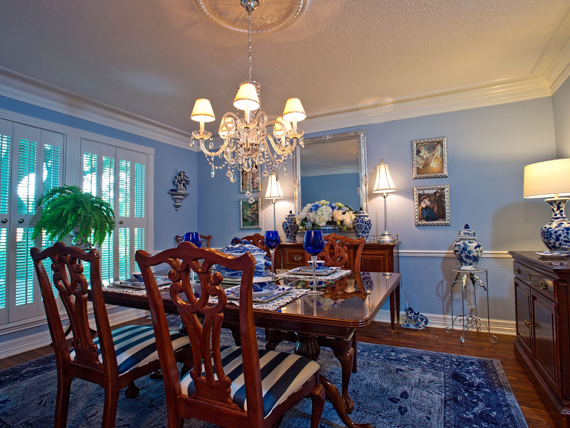 The formal dining area is picture perfect in baby blue with wide crown molding, a white shuttered picture window; illuminated with a beautiful crystal chandelier