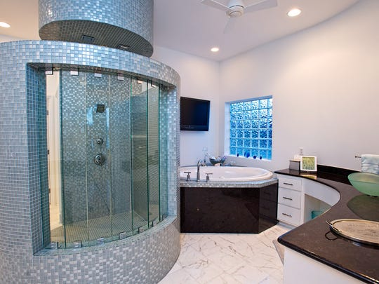 A unique tile and glass round shower enclosure with showers from above and side is a one of a kind; along with a garden tub and dual counters with glass vessel sinks make this the ultimate master bath.