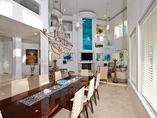 An amazing crystal ship chandelier hangs over the dining area table in the bright and wide open living space