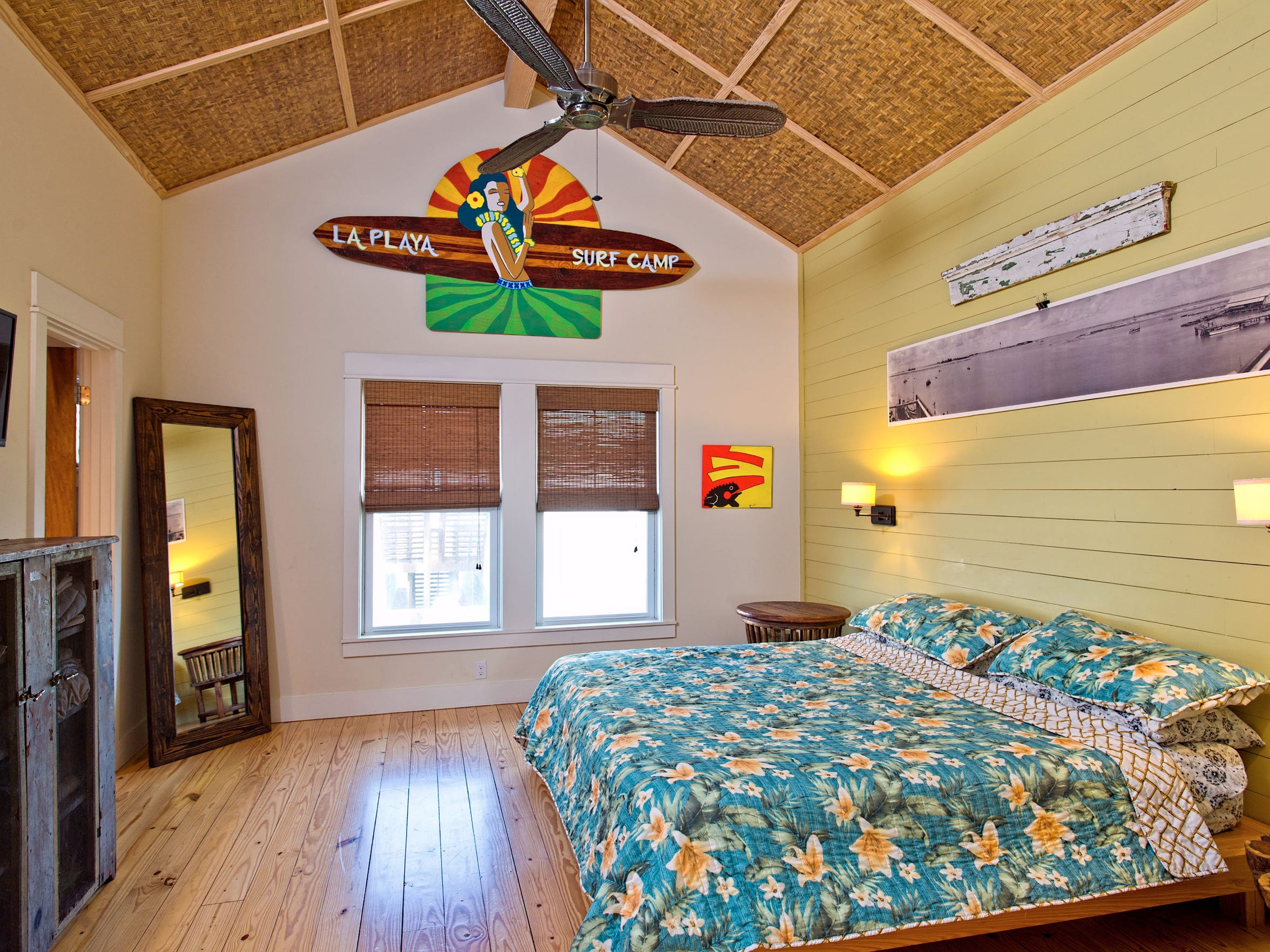 The master bedroom's bamboo covered high cathedral ceiling adds a Polynesian flair to the room which also has knotty pine wood plank flooring.