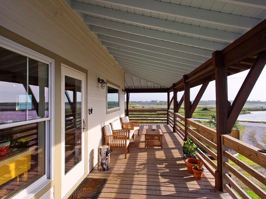 The upper deck wraps around the front and side the home and takes in panoramic views of Port Aransas' wet lands.