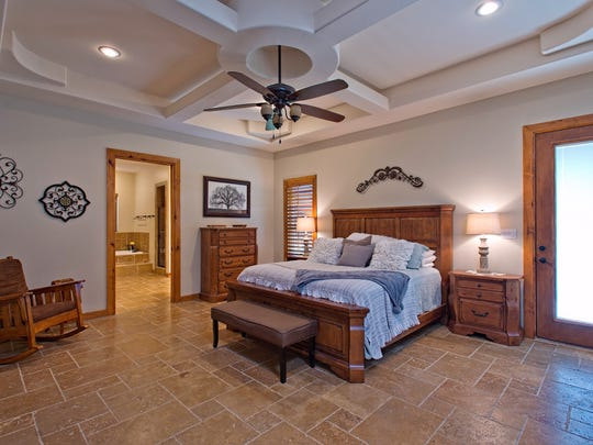 A spacious master bedroom with a recessed sculpted ceiling, travertine tile flooring and access to the patio, pool and pond