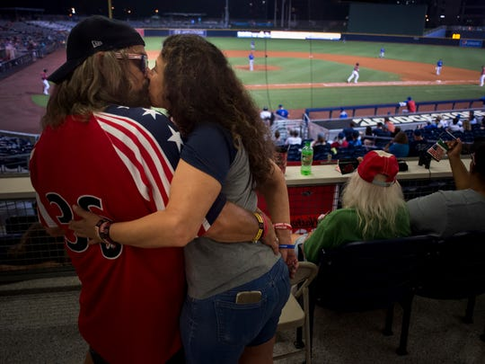"""Tony Slayden, originally of Mt. Juliet and now living in Berry Hill, and Kim Hodge, originally of Fairview and now living in Nashville, kiss while attending the Nashville Sounds' 4-1 victory against the Iowa Cubs at First Tennessee Park on Friday, July 6, 2018, in Nashville, Tenn. Slayden and Hodge, who are engaged, are both members of the """"Foul Bells,"""" a group of Sounds fans that often ring cow bells while cheering for the team. Slayden has been a regular attendee of Sounds games since 1987."""