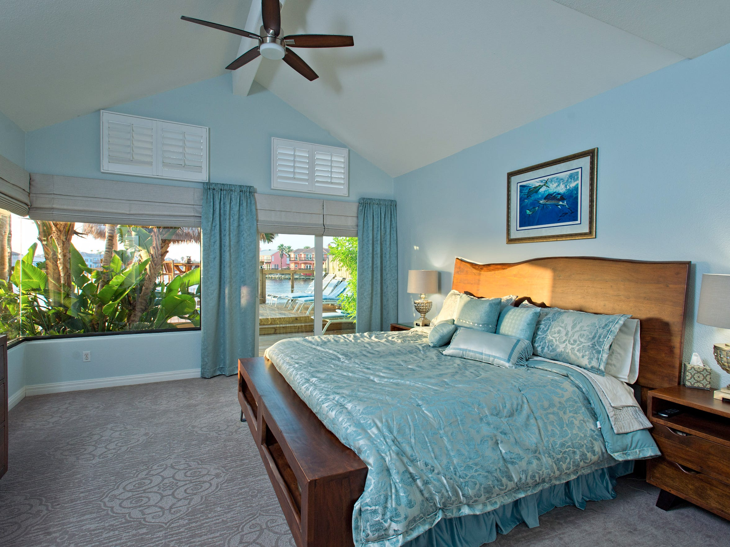 The spacious first floor master bedroom takes in water views from a set of sliding doors and a unique corner window and features a vaulted ceiling