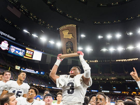 Lafayette Christian senior linebacker Martin Lee raises the Division IV state championship trophy after LCA beat Ascension Catholic 56-7 in the Mercedes-Benz Superdome on Dec. 6.