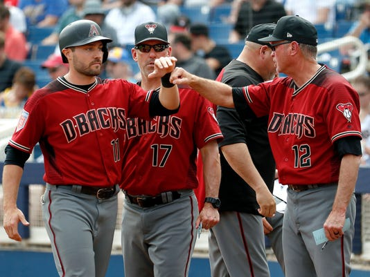 Arizona Diamondbacks' A.J. Pollock (11) is greeted by bench coach Jerry Narron (12) after scoring on a sacrifice fly by Jake Lamb during the first inning of a spring training baseball game against the Milwaukee Brewers, Thursday, March 8, 2018, in Phoenix. (AP Photo/Matt York)