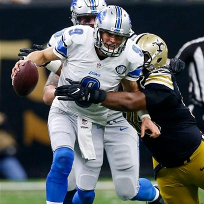 Lions quarterback Matthew Stafford (9) is brought down
