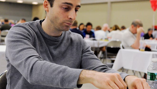 Will Anderson places his tiles on the board during the National Scrabble Championship, Wednesday, Aug. 13, 2014, in Buffalo.