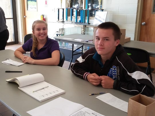 """Leigha Burnley and Micah Jones, 10th graders at Cumberland Christian School in Vineland, """"work"""" the polls for the school's mock election."""