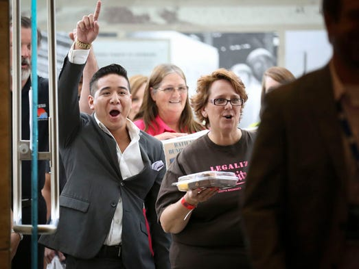 """Phillip Campos, left, of Tre Mentes sala of Des Moines and Michelle Kaiser of Allotta Brownies of Fremont, Nebraska, cheer as they enter the doors to the Iowa Events Center during an open casting call for the ABC show """"Shark Tank"""" in Des Moines, Iowa, Monday July 14, 2014."""