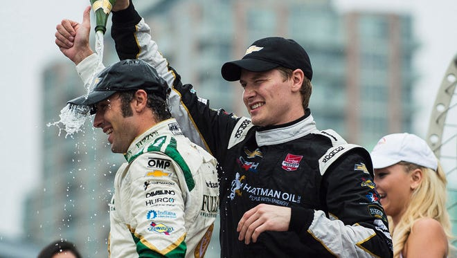 Honda IndyCar race winner Josef Newgarden of the United States pours champagne on his second place teammate Luca Filippi of Italy during the Hzwards ceremony in Toronto on Sunday, June 14, 2015. (Aaron Vincent Elkaim/The Canadian Press via AP) MANDATORY CREDIT