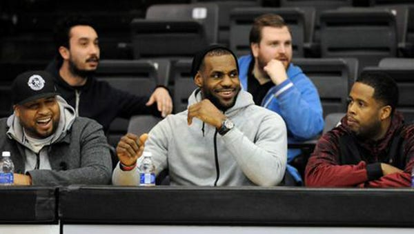 LeBron James sits courtside during Oakland's game Monday night.