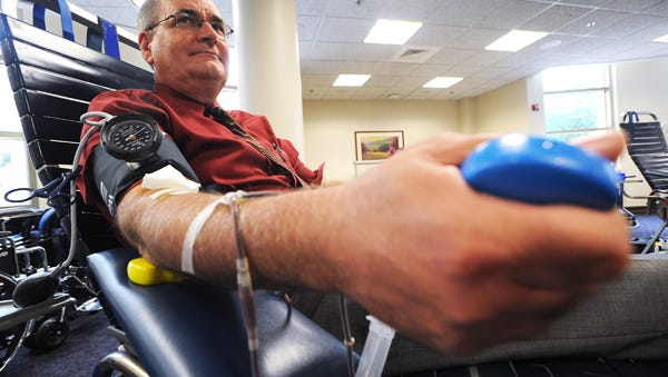 Larry Poch of Fond du Lac squeezes a piece of foam as he donates blood. Larry has been giving blood since he was in college and has donated almost seven gallons of blood in his life. He was donating at St. Agnes hospital during their blood drive. Wednesday, June 24, 2014.