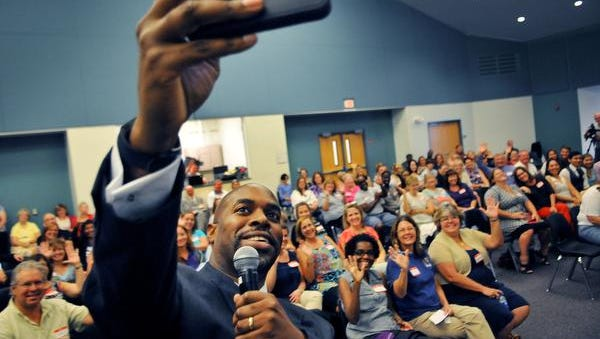 Desmond K. Blackburn, new Brevard Public Schools Superintendent, takes a selfie with the crowd during a meet and greet Tuesday night at  Space Coast Jr/Sr High.