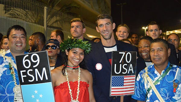 Team FSM flag bearer Jennifer Chieng, in red, meets Team USA flag bearer Michael Phelps at the Opening Ceremony of the 2016 Olympic Games in Brazil.