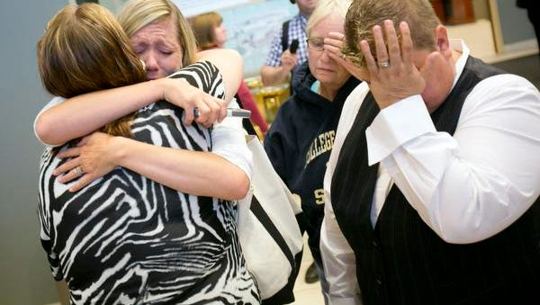 Mistie Tolman, left, cries as she gets a hug from friend Lisa Perry after she and her partner Karen McMillian, far right, were denied the opportunity for a marriage license inside the Ada County Courthouse in Boise, Idaho on Wednesday, Oct. 8, 2014.  U.S. Supreme Court Justice Anthony Kennedy has temporarily blocked an appeals court ruling that declared gay marriage legal in the states of Idaho and Nevada. The order came minutes after Idaho on Wednesday filed an emergency request for an immediate stay. The state's request said that without a stay, state and county officials would have been required to begin issuing marriage licenses to same-sex couples. (AP Photo/Idaho Statesman, Kyle Green)