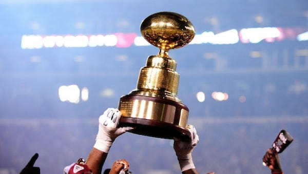 Mississippi State players hold up the Egg Bowl trophy.