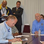 Gov. Rick Scott listens to status updates by law-enforcement and other emergency preparedness officials Thursday during a conference call in preparation for Hurricane Erika. Bryan Koon, director of the Division of Emergency Management, takes notes at left./Bill Cotterell, Democrat