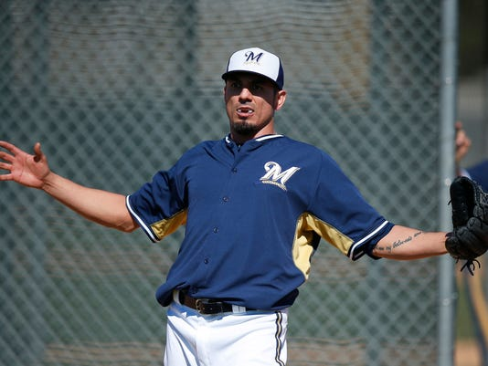 Milwaukee Brewers' Matt Garza stretches out as he adjusts his mouth guard between throwing pitches during Brewers spring training baseball practice, Monday, Feb. 17, 2014, in Phoenix. (AP Photo/Ross D. Franklin)