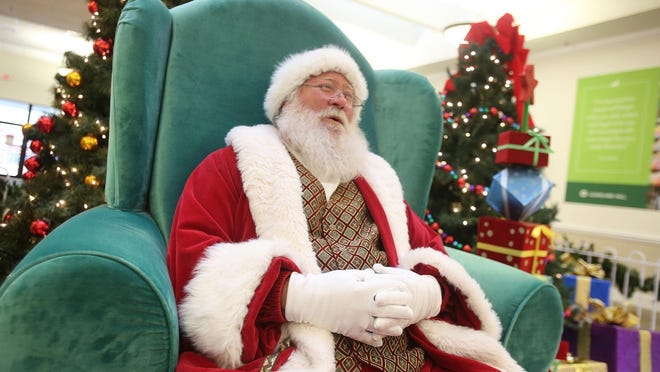Santa lets out a ho ho ho as shoppers pass by at Cleveland Mall in 2018. Santa will return to the mall this year but steps will be taken to keep everyone safe during the COVID-19 pandemic.