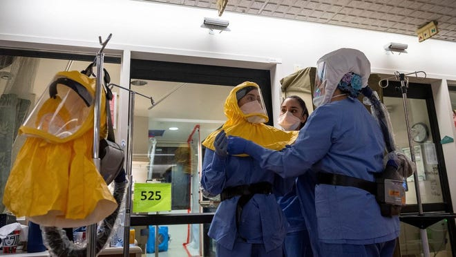 Nurses help each other put on their personal protective equipment before entering a patient's room in the COVID-19 unit in the Salinas Valley Memorial Healthcare System in Salinas, Calif.