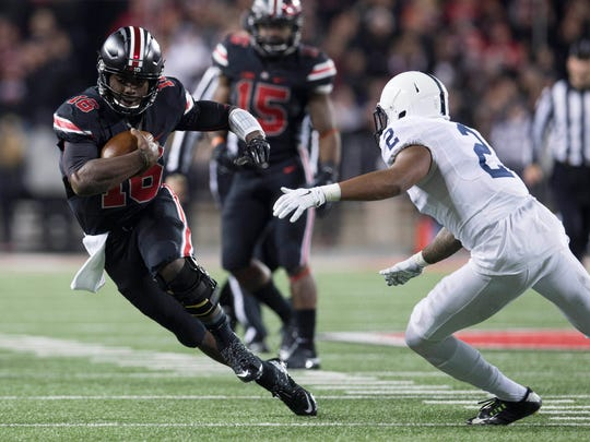 Ohio State quarterback J.T. Barrett swerves to avoid Penn State safety Marcus Allen in Saturday night's game.