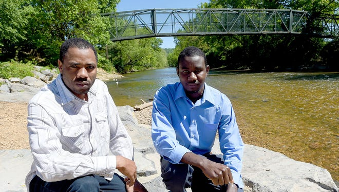 Mohamed Taha Mohamed and Abdelrahman Abshir kneel for a photo as the South River trickles calmly behind them in Waynesboro, Va., their home since January. They've been on the move since they were boys with the conflict in their home of Darfur, Sudan, pushing them out.
