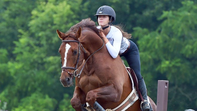 MacKensie Bowles, 17, of Staunton jumps with Chewy, a Zangersheide Warmblood, in the practice ring on Wednesday, July 5, 2017. Bowles, who also plays volleyball for Robert E. Lee High School, will be competing in the US junior hunter national championship later this month.