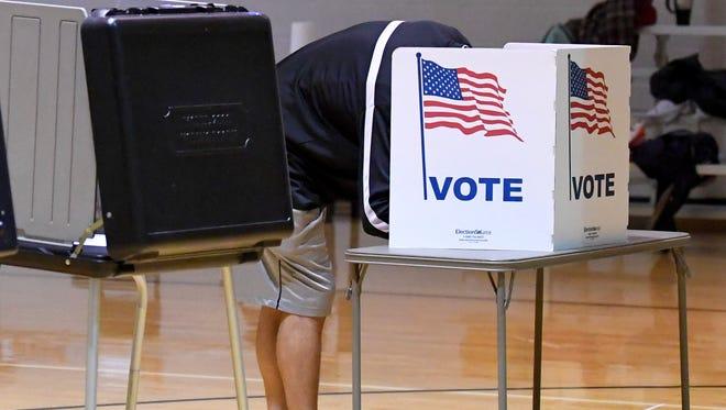Head down, a voter fills in his ballot at the Buffalo Gap precinct on Tuesday, Nov. 7, 2017.