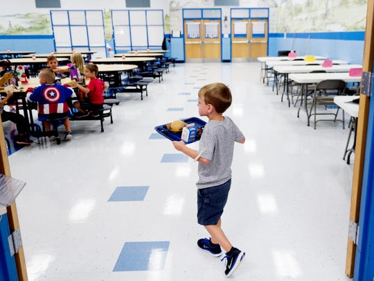 A student walks with their lunch to the tables at Gibbs Elementary School in Corryton, Tennessee on Tuesday, September 5, 2017. Knox County Schools has worked to reduce sodium content and increase whole grains in school lunches as well as offering more vegetables and fruits .