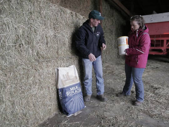 Greg and Rose Hartschuh add calf milk replacer and