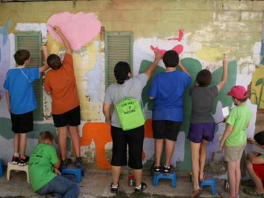 Art Outside the Box participants paint the exterior of a wall in Art Alley in July 2014 during a summer camp hosted by the San Angelo Museum of Fine Arts.