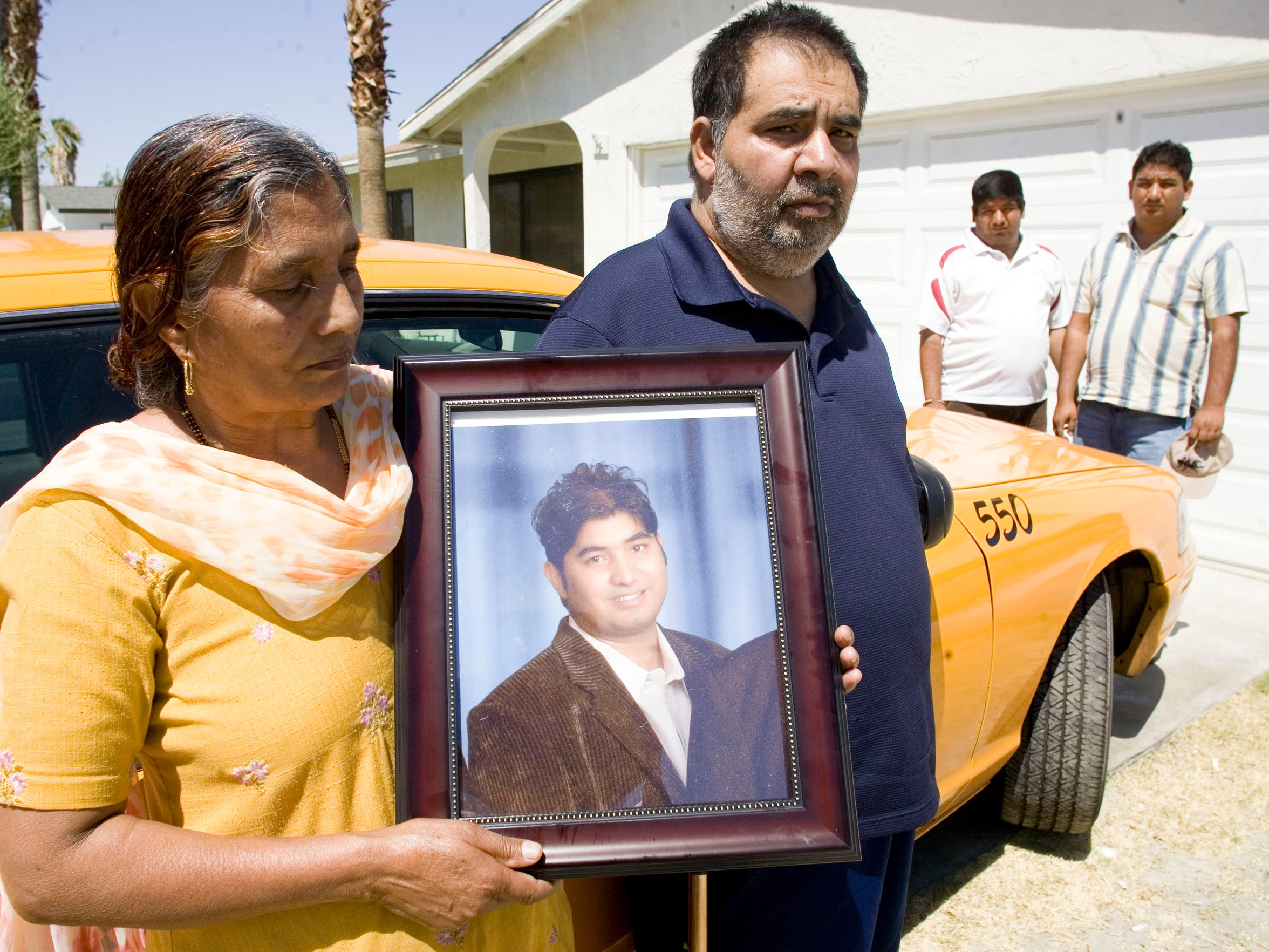 From left Malkit Kumar, holds a photo of her deceased
