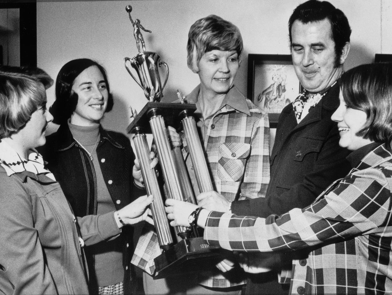 The IHSAA's Patricia Roy (center) shows the girls basketball state championship trophy to the representatives of the four teams at the 1976 state championship: Bloomfield's Nancy L. Woodward (from left), Warsaw's Janie N. Soyez, East Chicago Roosevelt's Matt Carr and Tech's Susan Jahnke.